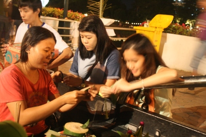 learning to make their own krathong along the street